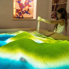 Enfant utilisant la projection interactive dans un bac à sable