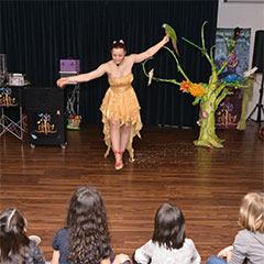 artistes magicienne réalisant un spectacle devant des enfants réunis pour un arbre de Noël