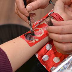 bras d'un enfant lors de la réalisation d'un tatouage en paillettes