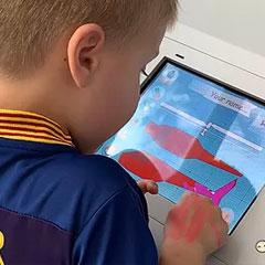 enfant dessin sur une tablette un avion